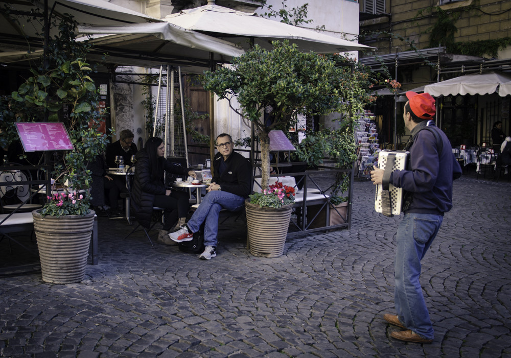 A musician playing in front of the restaurant in Monti